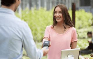 Mulher de pé oferecendo iZettle Pro para cliente colocar o cartão