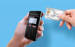 Mão segurando leitor Moviu enquanto outra segura cartão pré-pago