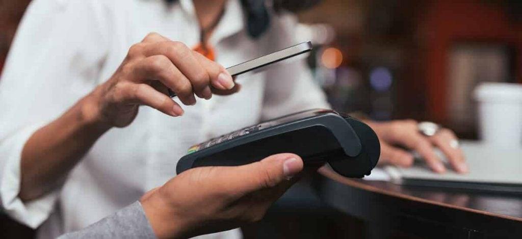 Mão segurando celular enquat outra segura máquina de cartão para pagamento via NFC