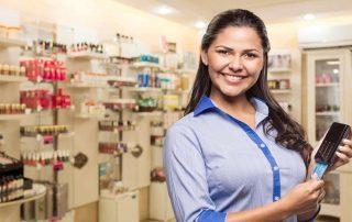 Mulher segurando máquina da Caixa Faz Crescer em uma farmácia