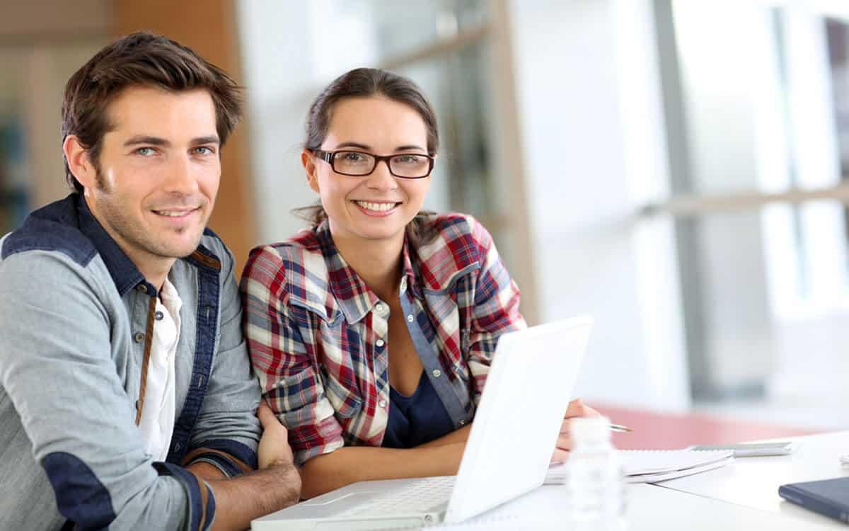 HOmem e mulher sentados em frente à laptop