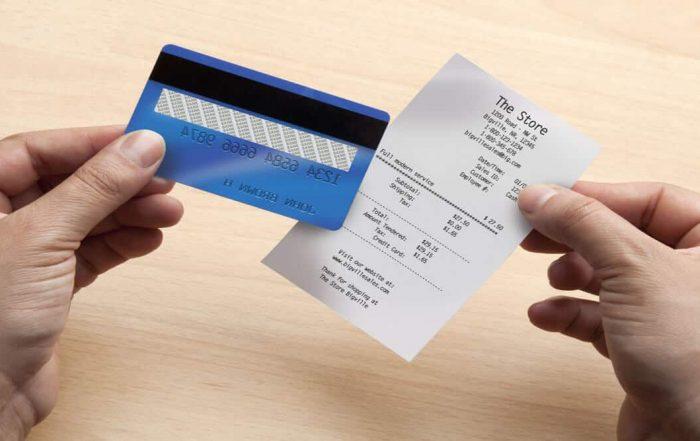 Mão segurando cartão e recibo