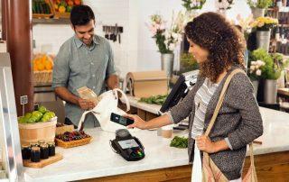 Mulher pganado em com Android Pay via NFC em maquina de cartao