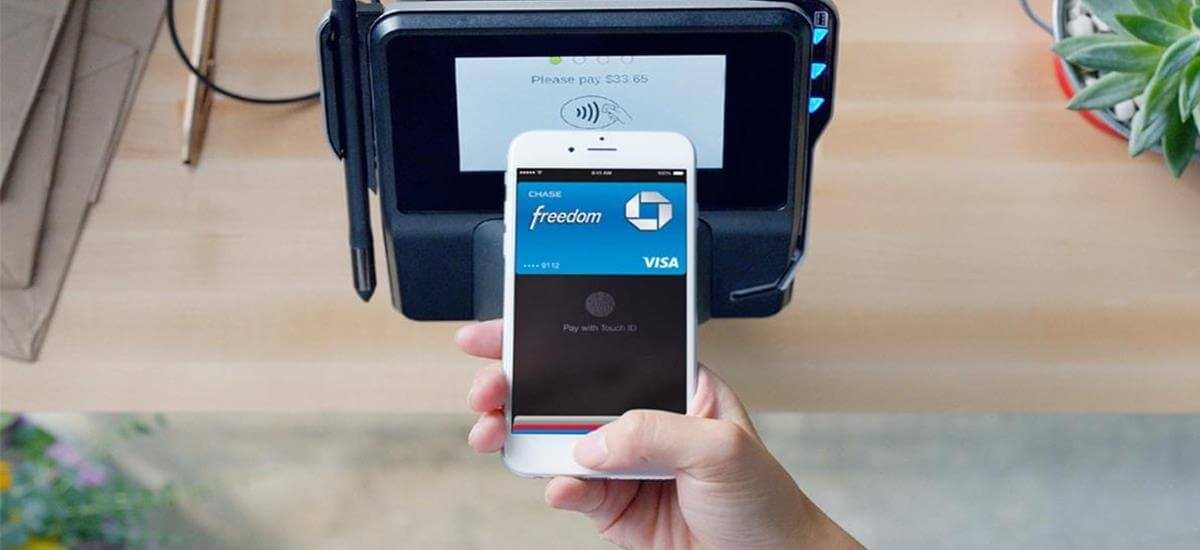 Mão com celular confirmando pagamento em máquina de cartão