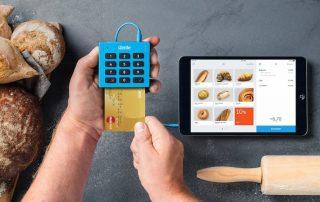 Mãos segurando iZettle Lite sobre mesa com pão, tablet e rolo de macarrão