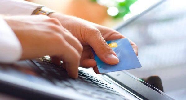Maõ digitando em laptop enquanto outra segura cartão