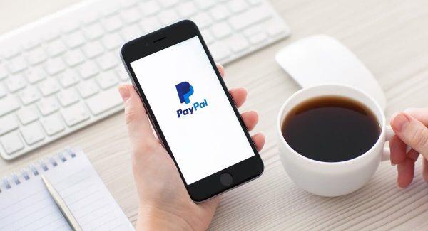 Mão segurando celular com logo PayPal na tela e outra segurando xícara de café