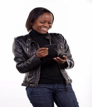 Mulher de pé segurando e olhando para cartão e celular