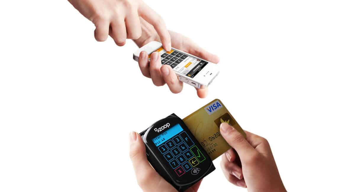 Mãos segurando Zoop Mobile com cartão enquanto outra digita no app do celular