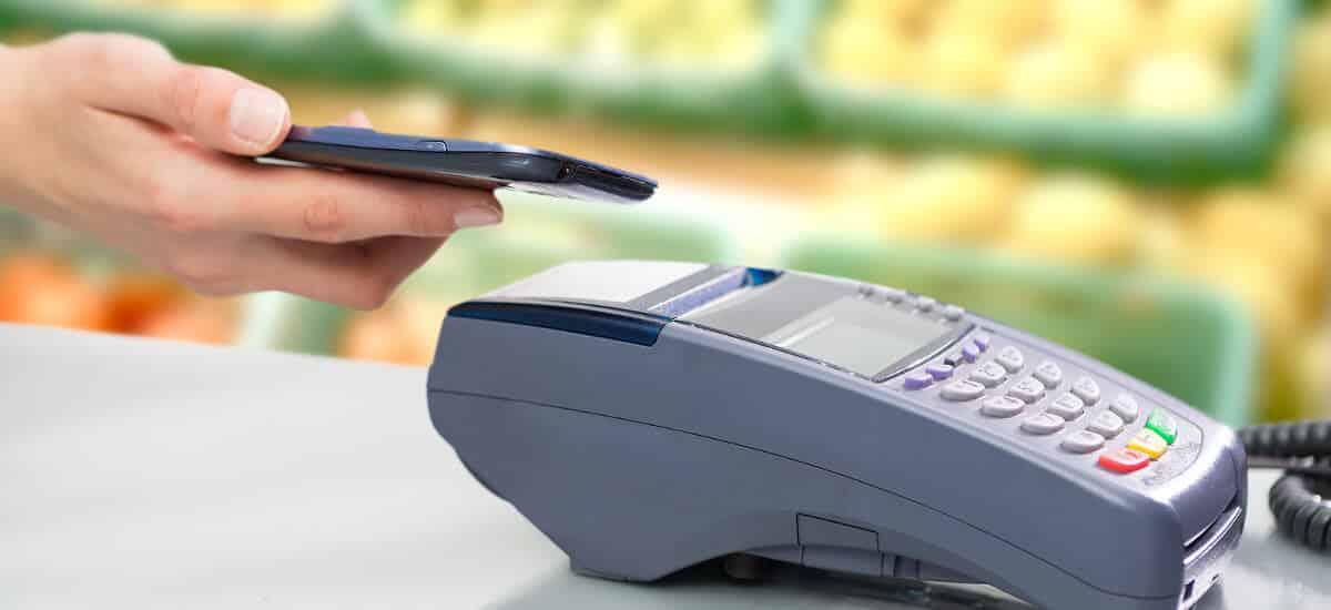 Mão posicionado cartão para pagamento NFC sobre máquina de cartão