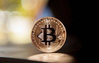 Moeda com logomarca Bitcoin de pé