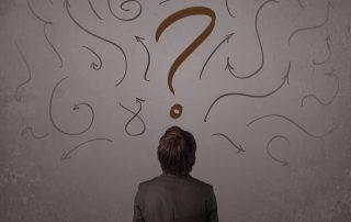 Homem olhando para mural cheio de interrogações