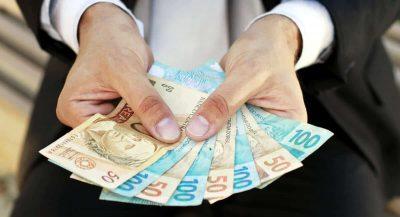 Mãos egurando várias notas de dinheiro