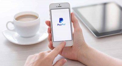 Maõs segurando celular com logomarca da PayPal com xícara de café e tablet ao fundo
