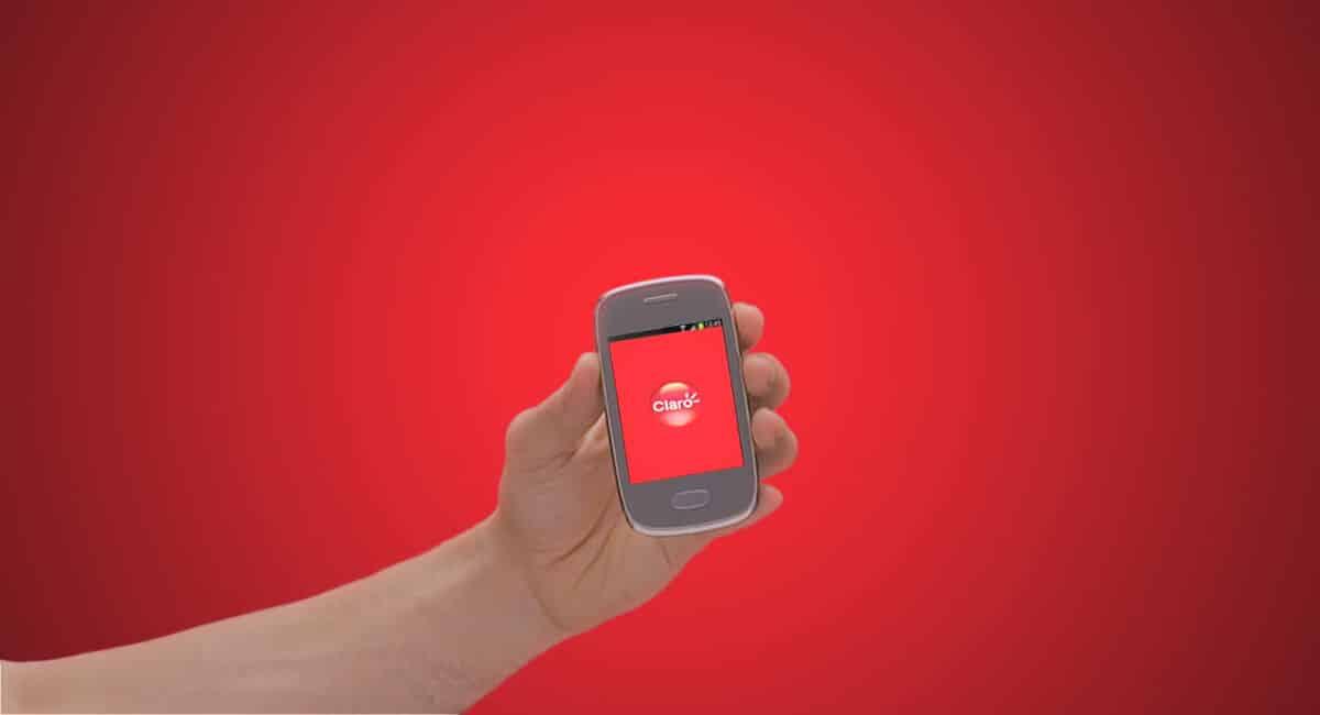Mão segurando celular mostrando logomarca Claro