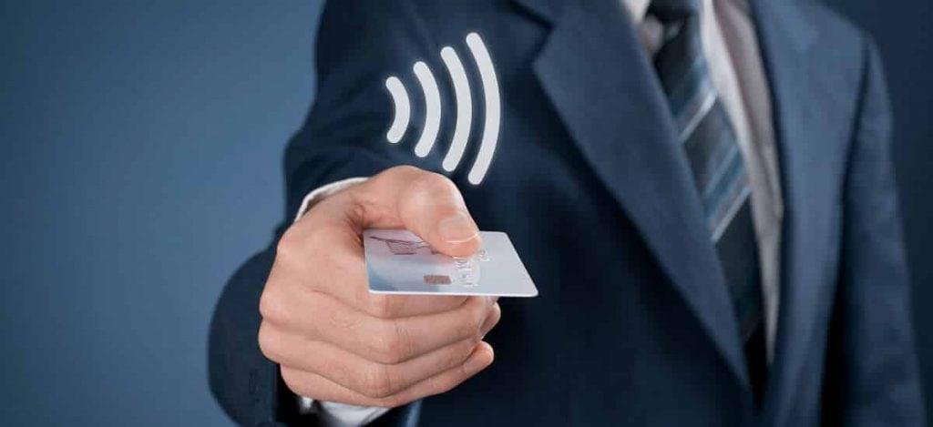 Homem de terno segurando cartão com símbolo NFC