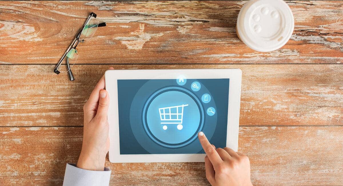 Mãos segurando tablet sobre mesa mostrando carrinho de compras