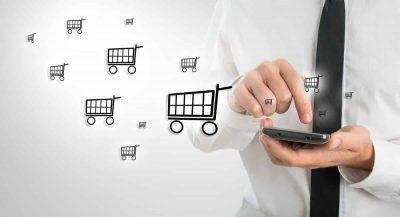 Homem digitando em celular do qual saem ilustrações de carrinhos de compras