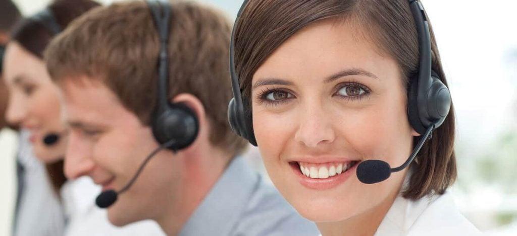 Mulher sorrindo com microfone de cabeça sentada ao lado de colegas