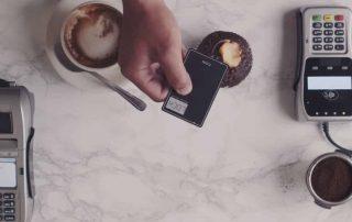Aparelho Coin sobre mesa com xícaras de café, bolinho, e duas máquinas de cartão