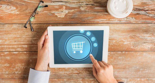 Mao segurando tablet que mostra ilustraçãode carrinho de compras