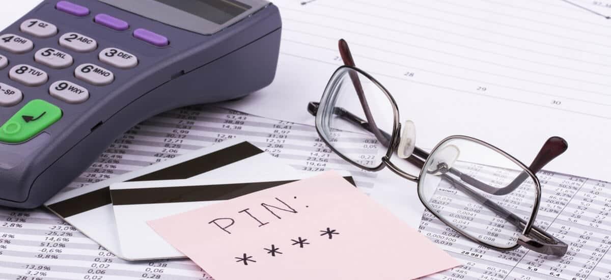 Calculadora, óculos, tickets com barra magnética, e papel com PIN sobre planilhas,