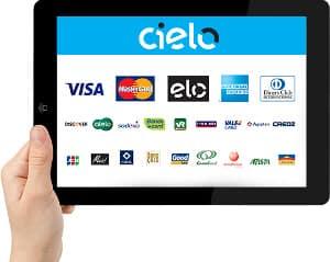 Mão segurando tablet mostrando Cielo Checkout