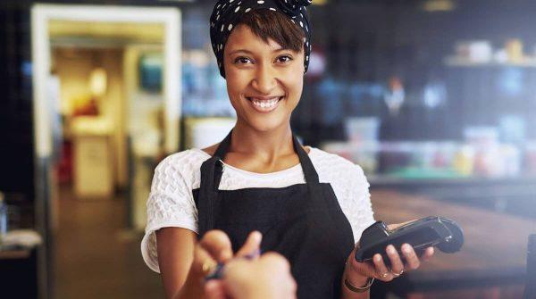 Vendedora sorridente com máquina na mão recebe cartão