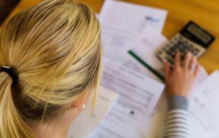 Mulher faznedo contas com calculadora e papéis sobre a mesa