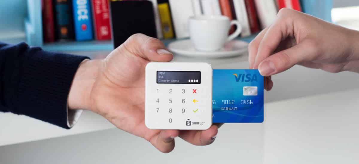 Mão segurando SumUp Top enquanto outra inseri cartão