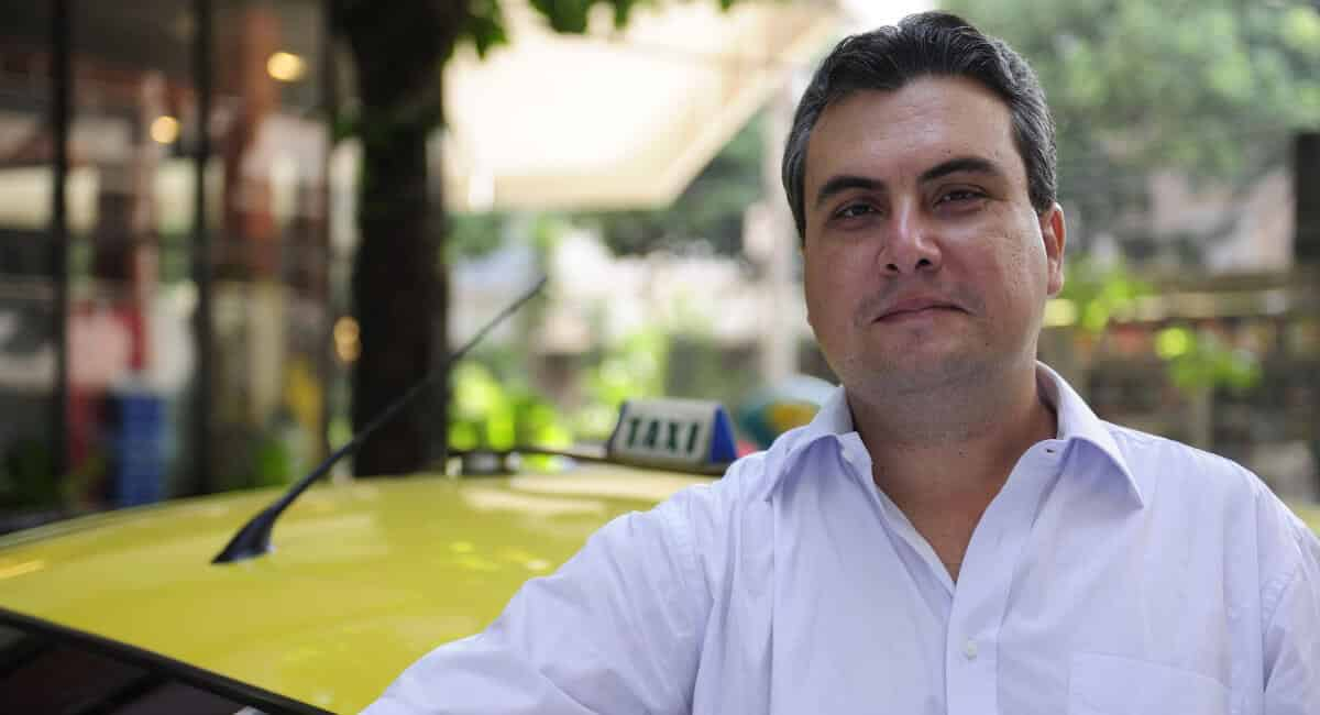 Homem enfrente à táxi