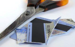 Tesoura ao lado de cartão cortado ao meio