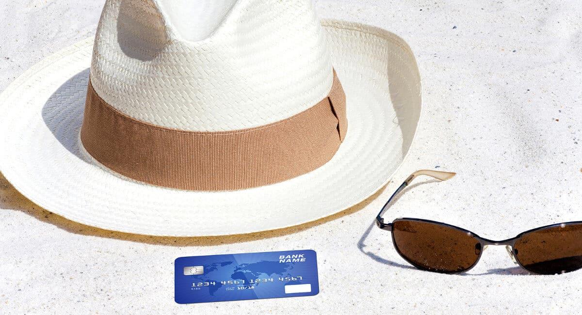 Chapéu de praia, cartão de crédito e óculos de sol