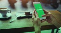 Mãos segurando celular com app PicPay sobre mesa de café