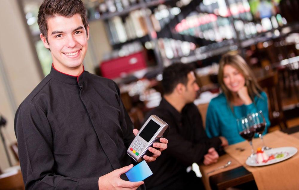 Rapaz segurando máquina de cartão e celular em frente à casal em mesa de restaurante