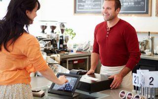 Mulher pagando via tablet como frente de caixa em frente ao vendedor