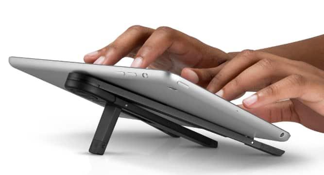 Mãos digitando em tablet no suporte Compass