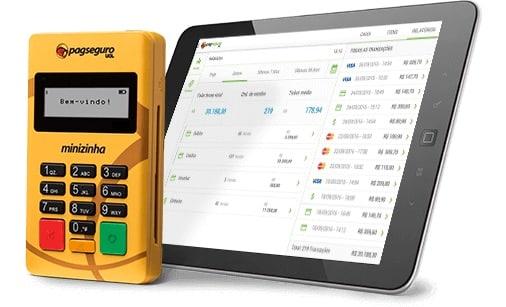 Minizinha do PagSeguro em frete `a tablet mostrando o app PagSeguro Vendas