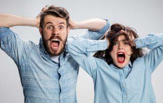 Homem em mulher com mãos na cabeça aparentando estresse