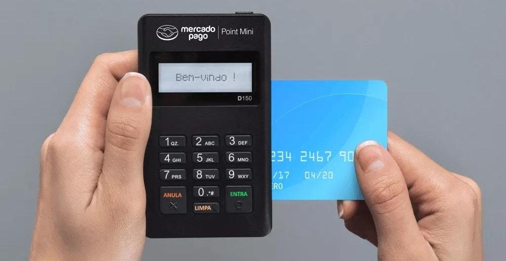mão segurando cartão e máquina mercado pago Point mini