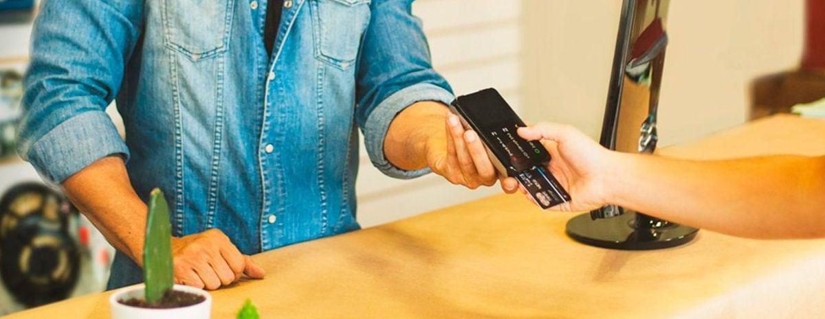 Vendedor segurando Point I para cliente pagar