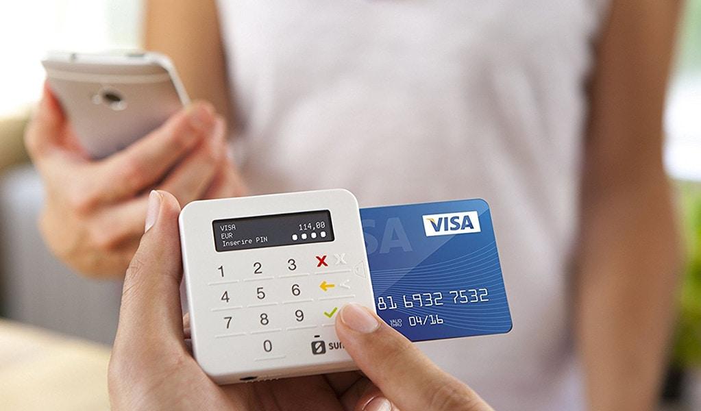Vendedor digitando venda na SumUp Top enquanto cliente segura celular