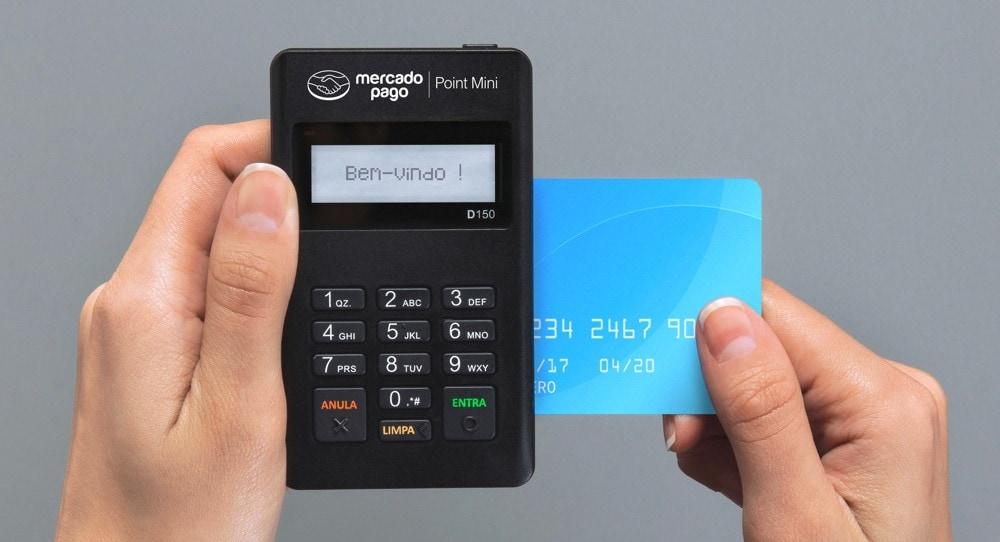 Mãos segurando Mercado Pago Point Mini e cartão