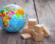 Globo terreste e caixas de papelão tipo exportação sobre mesa de madeira