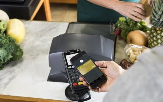 Mão fazendo pagamento com Android Pay em frutaria