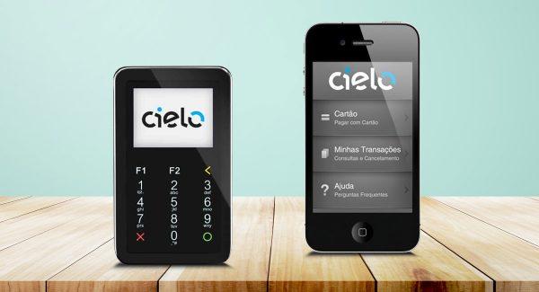 Cielo Mobile ao lado de celular mostrando app sobre uma mesa