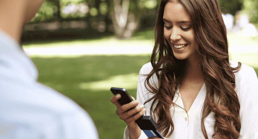 Mulher inserindo cartão no leitor em seu celular
