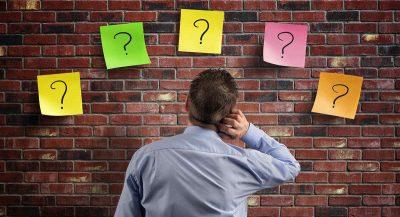 Homem olhando para cartões coloridos com interrogações em uma parede