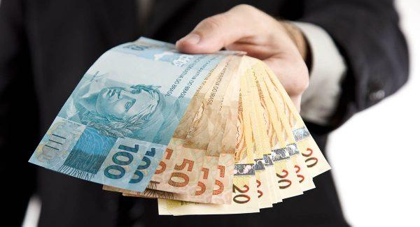 Mão segurando diversas notas de dinheiro