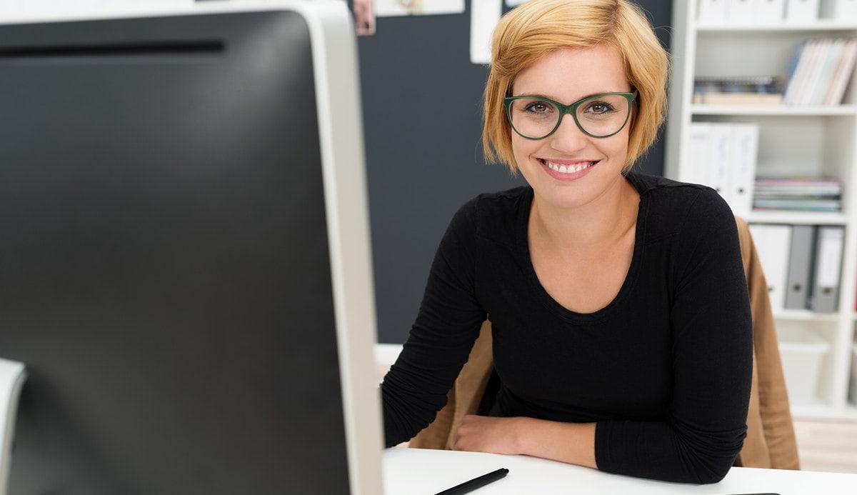 Mulher sentada de frente para um computador
